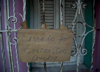 """Un cartel de """"Cerrado por coronavirus COVID-19"""" cuelga de la puerta de rejas de un negocio en La Habana, Cuba, el viernes 24 de abril de 2020. (AP Foto/Ismael Francisco)"""