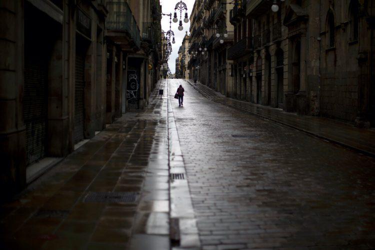 Un hombre camina por una calle vacía en el centro de Barcelona, España, el lunes 20 de abril de 2020, durante la cuarentena para combatir el coronavirus. (AP Foto/Emilio Morenatti)