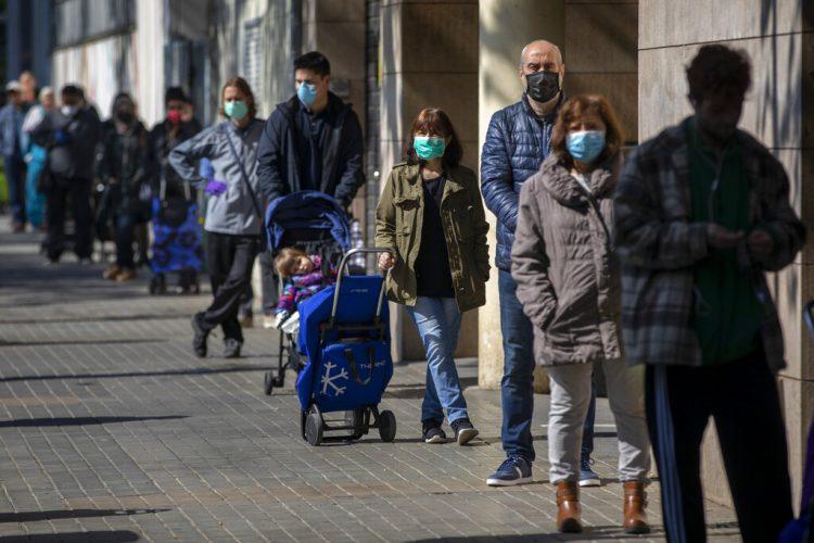 Personas con mascarillas se forman para comprar provisiones en una tienda durante el brote del coronavirus en Barcelona, España, el sábado 4 de abril de 2020. Foto: Emilio Morenatti / AP.