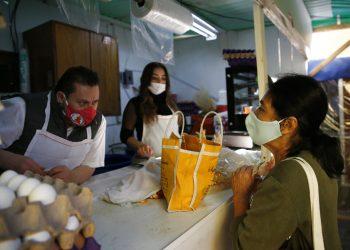 Un carnicero atiende a una clienta en la Ciudad de México el jueves 16 de abril de 2020. Todos portan nasobucos para protegerse Foto: Marco Ugarte/AP.