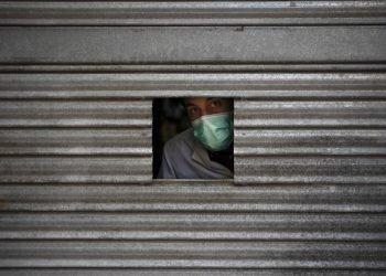 Un hombre con una mascarilla se asoma por una pequeña apertura en la puerta de una farmacia en espera de clientes en Igualada, España. Foto: Felipe Dana/AP.