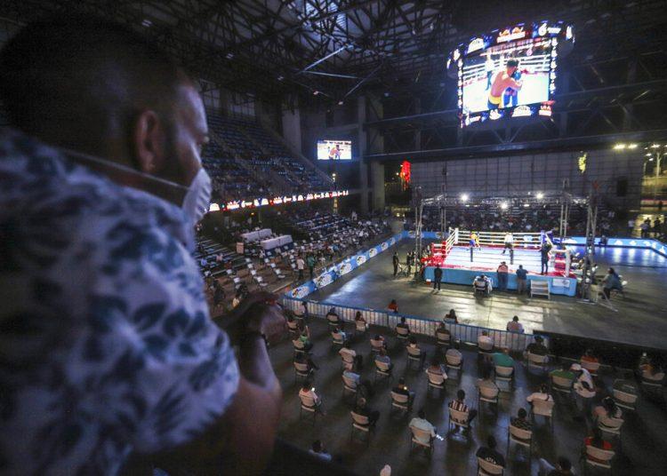 """Un hombre con mascarilla ve un combate en una velada de boxeo organizada por el bicampeón del mundo de boxeo Rosendo """"Búfalo"""" Álvarez en Managua, Nicaragua, el sábado 25 de abril de 2020.  Foto: AP/Alfredo Zúñiga."""