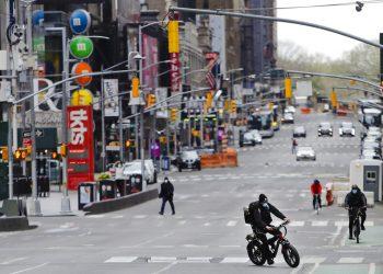 Peatones y ciclistas recorren la zona de Times Square en la ciudad de Nueva York, el viernes 17 de abril de 2020. Las calles de la ciudad están casi vacías mientras las personas prefieren mantenerse en casa para frenar los contagios de Covid-19. Las restrictiones, en vigencia desde el 22 de marzo, seguirán por lo menos hasta el 15 de mayo. Foto: AP /Frank Franklin II)