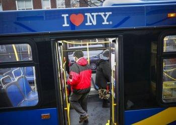 Pasajeros lucen máscaras y otra protección en un autobús de transporte público en la ciudad de Nueva York, que opera sin cobro, el viernes, 24 de abril del 2020.  (AP Foto/John Minchillo)