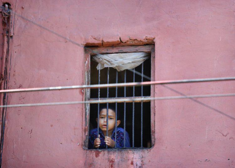 Un niño mira por la ventana de su casa en el barrio viejo de Nueva Delhi, India. Foto: Manish Swarup/Ap.