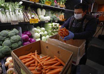 Un empeado luciendo una máscara protectora y guantes contra el COVID-19, coloca zanahorias en los estantes en el Gus's Community Market el viernes, 27 de marzo del 2020, en San Francisco.  (AP Foto/Ben Margot)