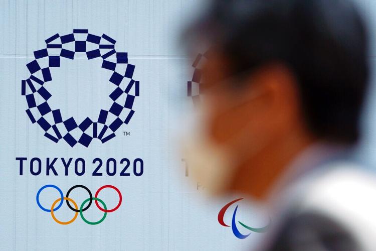 Un hombre con una mascarilla protectora contra infecciones respiratorias como la COVID-19 pasa junto al logo de los juegos olímpicos Tokio 2020. Foto: Eugene Hoshiko / AP / Archivo.