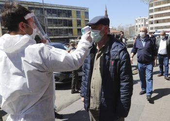 Un empleado de un supermercado le toma la temperatura a los clientes en Ankara, Turquía, el 17 de abril del 2020. (AP Photo)