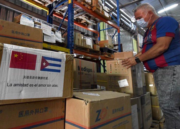 Un trabajador inspecciona cajas con insumos sanitarios llegados desde China para la contención de la pandemia por el nuevo coronavirus en Cuba. Foto: Joaquín Hernández / Xinhua / Archivo.