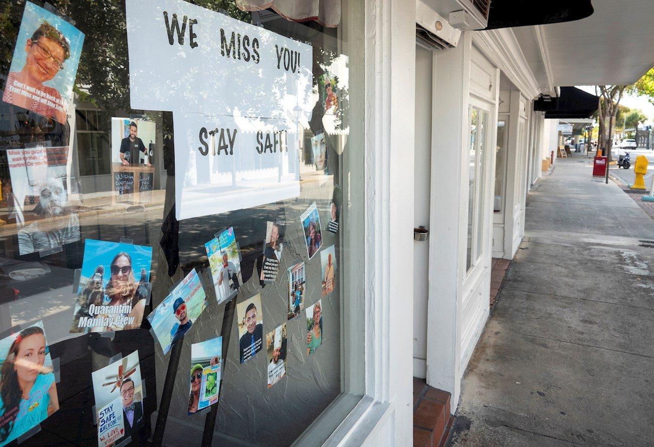 """Vista del mensaje """"Los extrañamos, sigan a salvo"""" a la entrada de un negocio en una vacía calle Duval, la más concurrida para el turismo en Cayo Hueso, Florida. Foto: Cristóbal Herrera / EFE."""