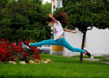 Una niña con mascarilla salta en una calle en Córdoba, ESpaña, este domingo. Foto: Salas/EFE.