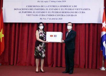 La embajadora cubana en Hanoi, Lianys Torres (i), recibe simbólicamente la donación de 5 mil toneladas de arroz de Vietnam a Cuba. Foto: @EmbaCubaVietnam / Twitter.