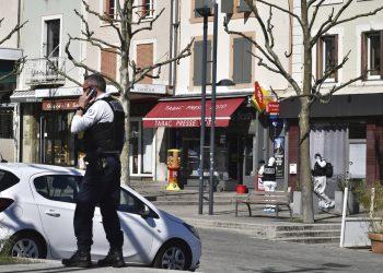 Un policía llama por celular después de que un hombre con un cuchillo atacara a residentes que salieron de compras en una población sometida a cuarentena el sábado 4 de abril de 2020 en Romans-sur-Isere, en el sur de Francia. Foto: AP.