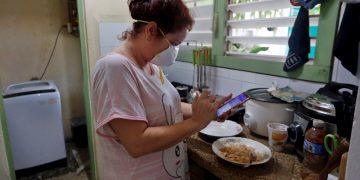Una mujer revisa su teléfono en la cocina de su casa el 6 de abril de 2020 en La Habana. Foto: EFE/Ernesto Mastrascusa