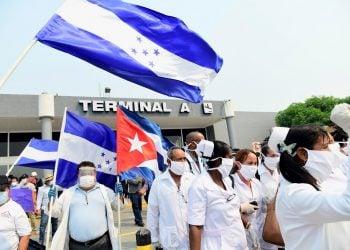 Integrantes de una brigada médica de Cuba saludan tras aterrizar en el Aeropuerto Internacional Ramón Villeda Morales de San Pedro Sula, Honduras. Foto: EFE/ José Valle.