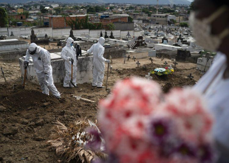 Trabajadores de un cementerio, vestidos con trajes de protección, cierran la tumba de Ana María, una ayudante de enfermería de 56 años que falleció a causa del coronavirus, en Río de Janeiro, Brasil, el 28 de abril de 2020.  Foto: AP/Leo Correa.