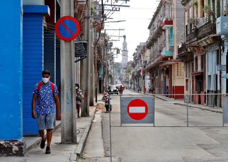 Un hombre con tapabocas pasa por una calle con acceso restringido por la Covid-19 en La Habana. Foto: Ernesto Mastrascusa / EFE.