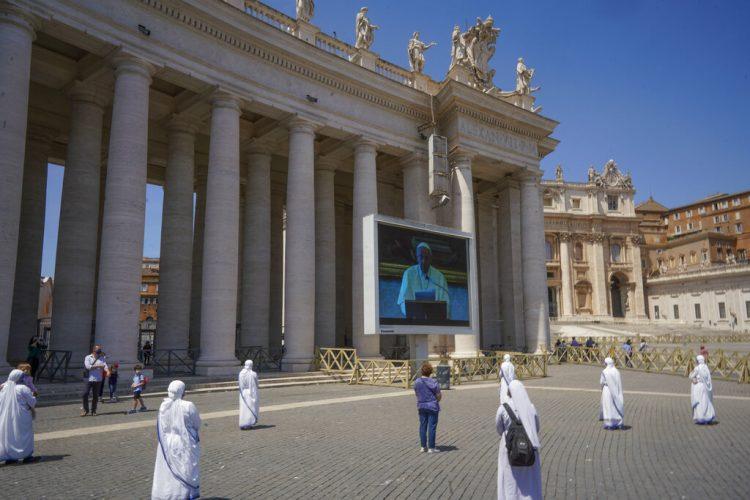 Monjas y fieles respetan el distanciamiento social mientras observan al papa Francisco recitar una oración a través de una pantalla en la plaza de San Pedro, en el Vaticano, el domingo 24 de mayo de 2020. (AP Foto/Andrew Medichini)