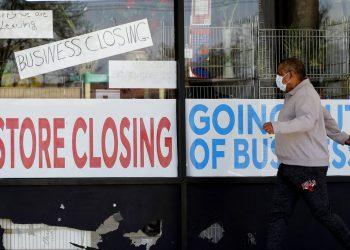 Fotografía de archivo del 21 de mayo de 2020 de un hombre con mascarilla caminando junto a un negocio con letreros de próxima clausura debido a la pandemia de COVID-19 en Niles, Illinois. Foto: AP/Nam Y. Huh/Archivo.