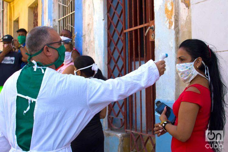 Tomando la temperatura antes de hacer prueba del Covid-19 en un cuadrante de Los Sitios, en La Habana. Foto: Otmaro Rodríguez