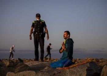 Un agente de policía habla con un hombre en una playa reabierta para actividades deportivas en Barcelona. Foto: Emilio Morenatti/AP