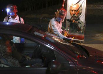 Trabajadores con trajes protectores desinfectan autos que entran a un autocine situado junto a la torre Milad, en Teherán, el viernes 1 de mayo del 2020. Irán es el epicentro de la pandemia del Covid-19 en la región. Foto: AP/Vahid Salemi.