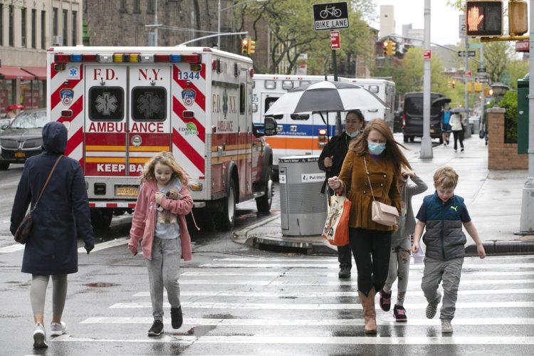 Varias personas, entre ellas niños, caminan frente al NewYork–Presbyterian Brooklyn Methodist Hospital en la ciudad de Nueva York, el 6 de mayo del 2020. Foto: Mark Lennihan / AP.