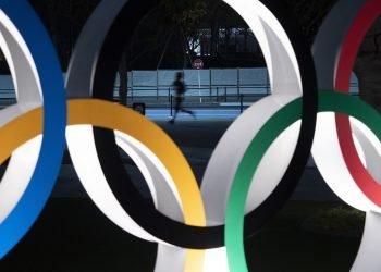 Un hombre corre por detrás de los anillos olímpicos, en Tokio. Foto: Ap/Jae C. Hong, archivo.