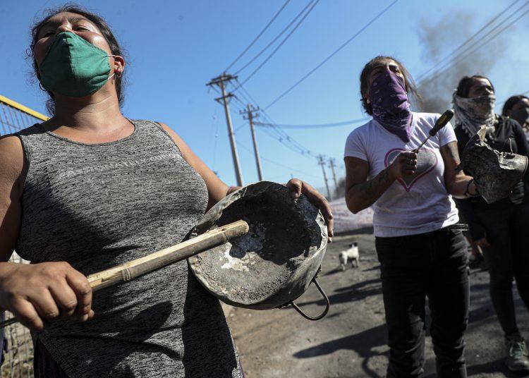 Manifestantes reunidas cerca de una barricada en llamas, durante una protesta pidiendo más ayuda alimentaria del gobierno en la pandemia del coronavirus, en un vecindario de Santiago de Chile, el martes 26 de mayo de 2020.  Foto: Esteban Félix/AP