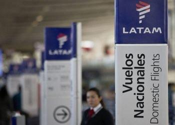 Una empleada de LATAM Airlines junto a los mostradores de facturación en el aeropuerto de Santiago de Chile. Foto: Esteban Félix/AP