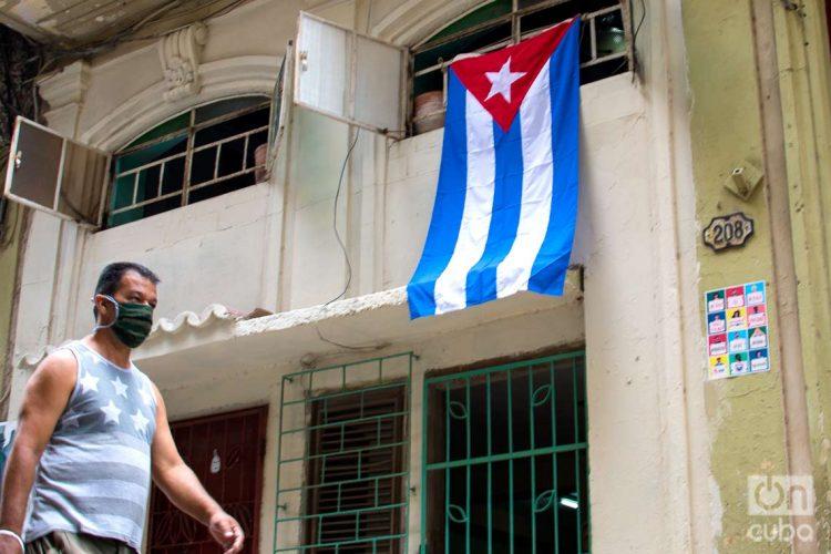 Un hombre pasa cerca de una bandera cubana colgada en una calle de La Habana, el 1 de mayo de 2020. Foto: Otmaro Rodríguez / Archivo.