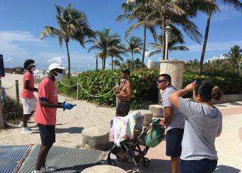 Unos jóvenes revisan las máscaras de unas personas a su llegada a la playa de Miami Beach, Florida, el 10 de junio de 2020. Foto: Ivonne Malaver / EFE.