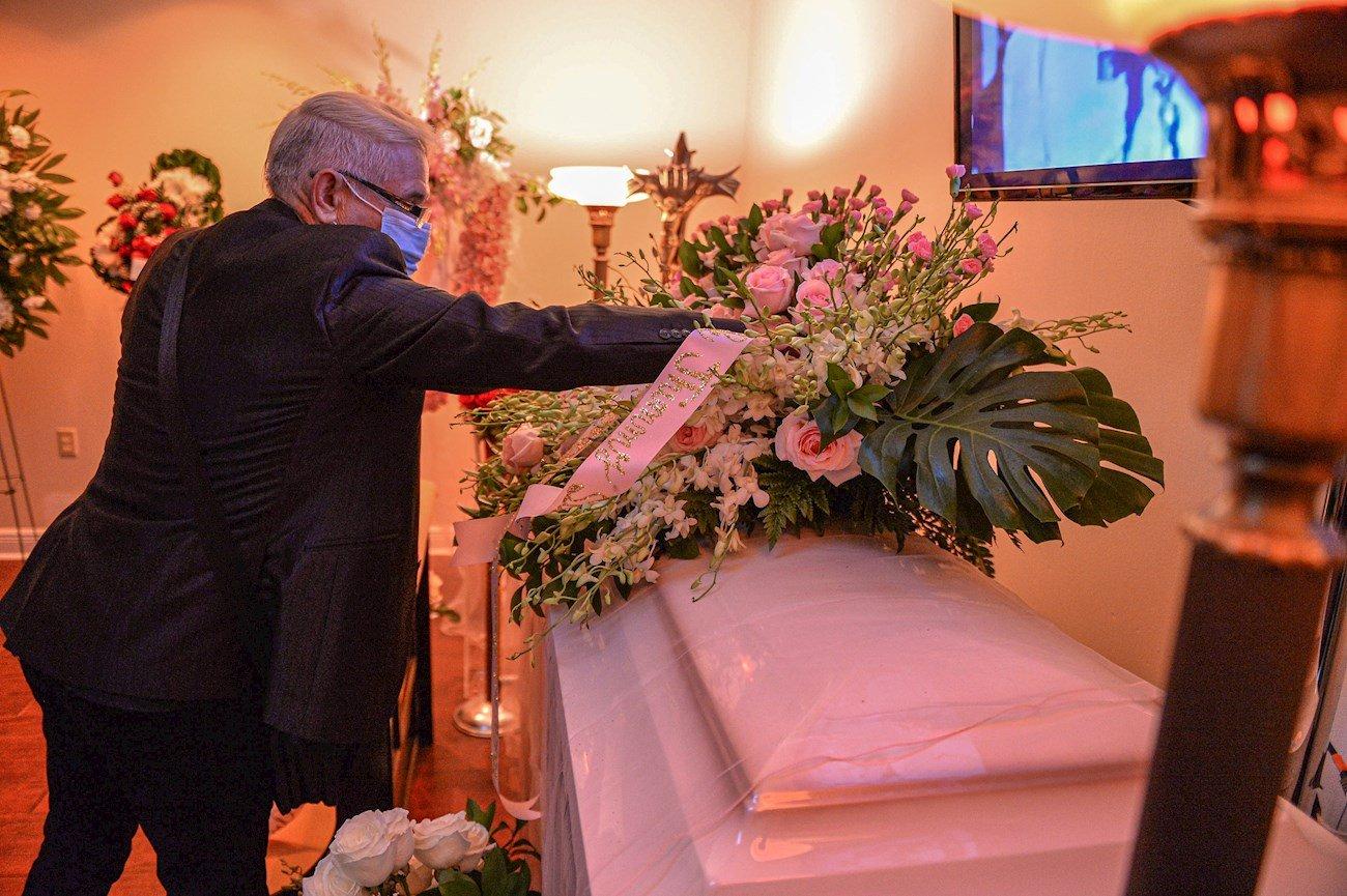 """Un hombre toca el féretro de la fallecida cantante Rosita Fornés este viernes durante su velorio en la Funeraria Auxiliadora Nacional en Miami, Florida (EEUU). La actriz, cantante y vedete cubana Rosita Fornés, fallecida en Miami a los 97 años, fue despedida este viernes por sus familiares, amigos y admiradores en una funeraria de la ciudad y """"muy pronto"""" sus restos serán llevados a Cuba, según dijo a EFE José Antonio Jiménez, esposo de la única hija de la artista. EFE/Giorgio Viera"""