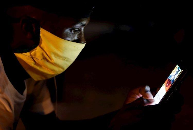 Un joven con tapabocas observa su teléfono en Cuba. Foto: Yander Zamora / EFE / Archivo.