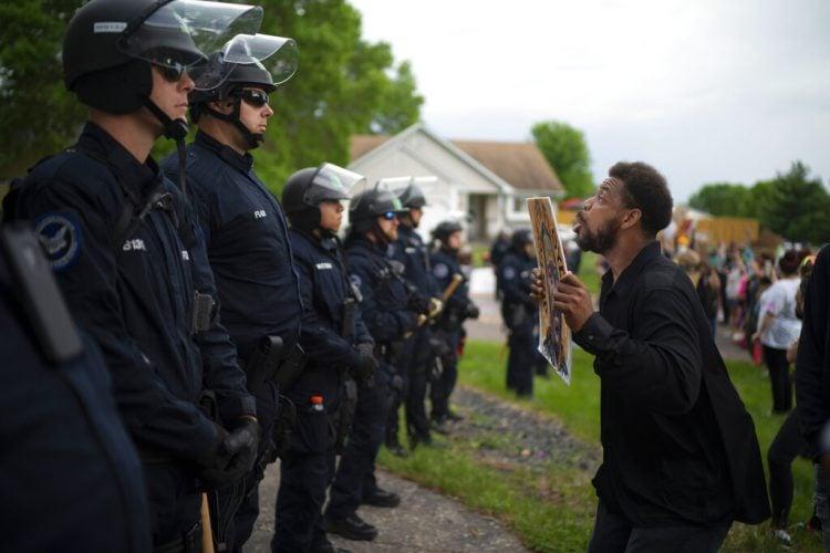 Un manifestante sostiene una pancarta mientras salta en repetidas ocasiones para que los policías que se encuentran al fondo puedan verlo el miércoles 27 de mayo de 2020 en la casa del agente Derek Chauvin, quien fue despedido de la policía de Minneapolis, a las afueras de Oakdale, Minnesota. Foto: Jeff Wheeler/Star Tribune vía AP