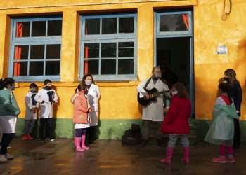 Usando una mascarilla en medio de la pandemia del nuevo coronavirus, un maestro le canta a su clase en el primer día de vuelta a la escuela rural cerca de Empalme Olmos, Uruguay, el lunes 1 de junio de 2020. Foto: Matilde Campodonico/ AP