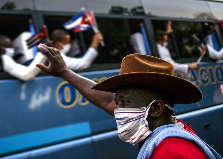 Un hombre saluda a un grupo de doctores, parte de la primera brigada médica cubana del Contigente Henry Reeve, el lunes 8 de junio de 2020 después de que llegaron a La Habana, Cuba. Los médicos habían viajado a Italia para ayudar con la emergencia por el COVID-19. Foto: Ramón Espinosa/AP
