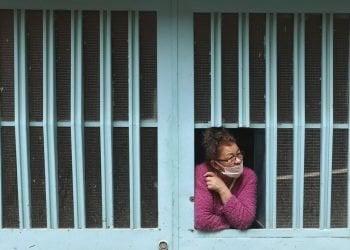 Una mujer observa desde la ventana de su casa mientras espera recibir comida gratis del gobierno de la ciudad el viernes 12 de junio de 2020, en Bogotá, Colombia, donde continúan las medidas de prevención por el coronavirus. (AP Foto/Fernando Vergara)