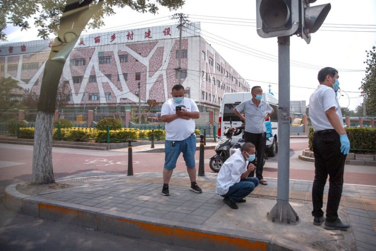 Varias personas utilizan mascarillas para protegerse del nuevo coronavirus en una calle afuera del mercado mayorista de alimentos Xinfadi en Beijing, el sábado 13 de junio de 2020. El mercado fue cerrado debido a que se detectaron siete casos locales de coronavirus en los últimos días, según las autoridades. (AP Foto/Mark Schiefelbein)