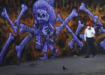 El responsable de varios cementerios públicos camina ante un mural de un esqueleto y huesos en el exterior del Panteón San Nicolás Tolentino, Iztapalapa, Ciudad de México. Foto: Marco Ugarte/AP.