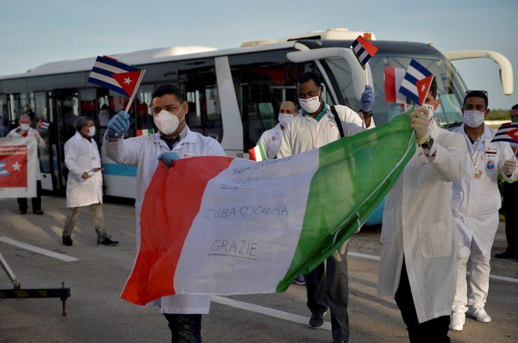 Médicos cubanos ondean banderas cubanas e italianas tras su llegada desde Europa este lunes, a La Habana. Foto: EFE/Yamil Lage.