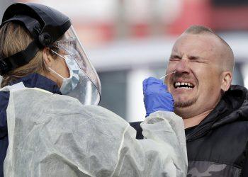 Un hombre reacciona mientras personal médico hace pruebas a diagnósticas de coronavirus en un puesto en el estacionamiento de un supermercado en Christchurch, Nueva Zelanda. Foto: Mark Baker/AP, Archvo