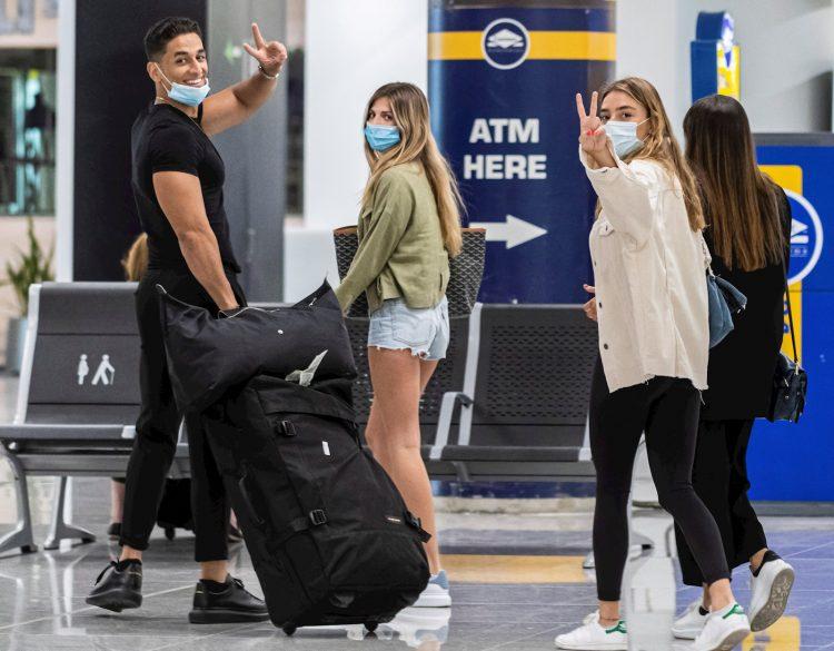 Viajeros ataviados con mascarillas a su llegada al Aeropuerto de Palma de Mallorca, este domingo, durante el primer día del fin del estado de alarma, en el que se espera la llegada de 25 vuelos internacionales. Foto: Cati Cladera / EFE.