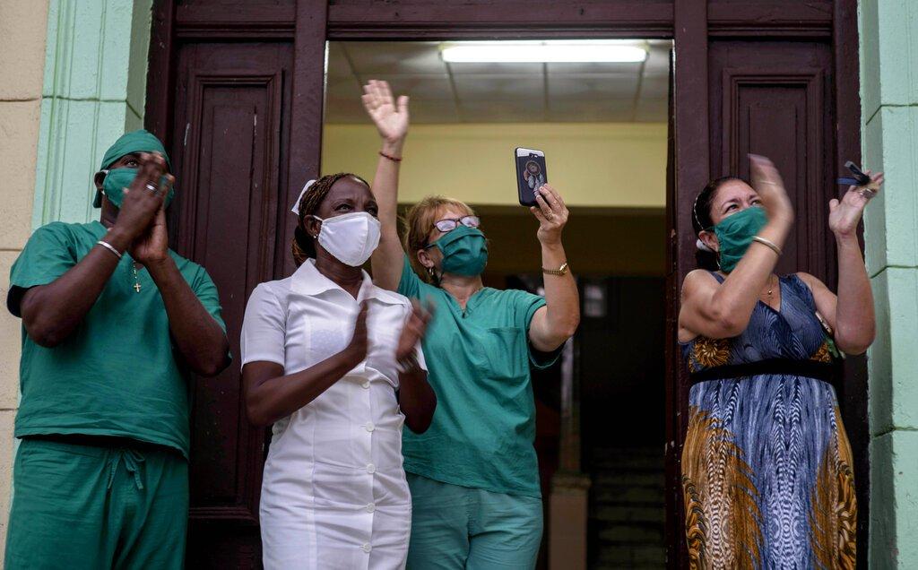 Personal médico aplaude al tenor cubano Andrés Sánchez Joglar, quien serena a sus vecinos desde el balcón de su apartamento en La Habana, el domingo 31 de mayo de 2020. Foto: AP/Ramón Espinosa.