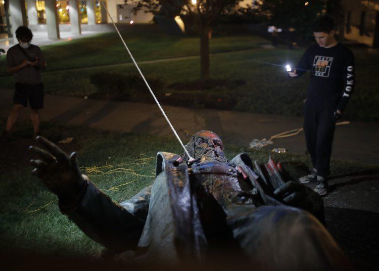 Un hombre usa su celular para grabar la estatua de Albert Pike, la única de un general del ejército confederado en la capital de Estados Unidos, después de que fue derribada por manifestantes e incendiada en Washington en las primeras horas del sábado 20 de junio de 2020. Foto: Maya Alleruzzo. AP