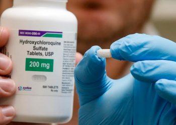 Un farmacéutico sostiene una píldora de hidroxicloroquina. Foto: AFP/George Frey.