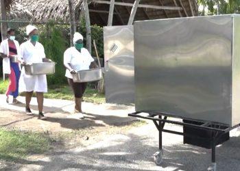 El robot cubano Palmiche (derecha) es utilizado para repartir alimentos en el centro de aislamiento de la CUJAE, en La Habana, durante la pandemia de coronavirus. Foto: Captura de pantalla.