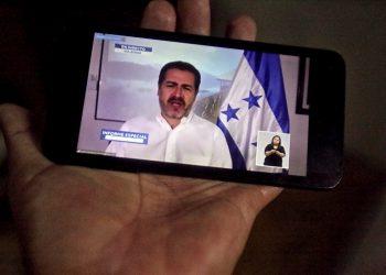 Un hombre mira a través de su móvil la transmisión de la comparecencia del presidente de Honduras, Juan Orlando Hernández, mientras anuncia que ha contraído la COVID-19, al igual que su esposa, Ana García en Tegucigalpa. Foto: Gustavo Amador/EFE
