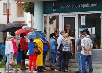 Varias personas hacen fila ante una sucursal habanera del Banco Metropolitano, uno de los emisores de tarjeta de crédito en dólares en Cuba . Foto: Yander Zamora / EFE.
