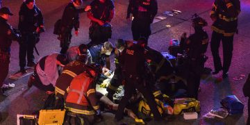 Trabajadores de emergencias atienden a una persona herida tras un atropello en una protesta en la Interestatal 5 en Seattle. Dawit Kelete, de 27 años, fue detenido y acusado de dos delitos de agresión con vehículo, según las autoridades. (James Anderson via AP)